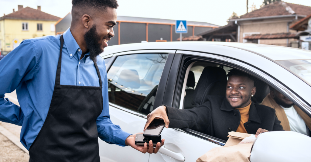 Customer using contactless payment to pay a retailer for a curbside pickup order